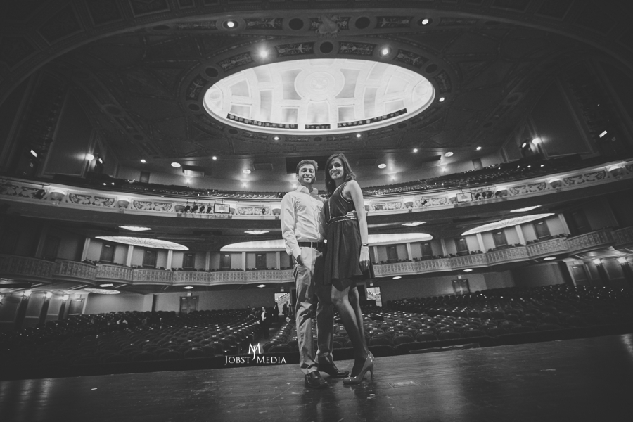 Indian Wedding Photographers Michigan engaged couple on the stage posing in an auditorium and looking amazing