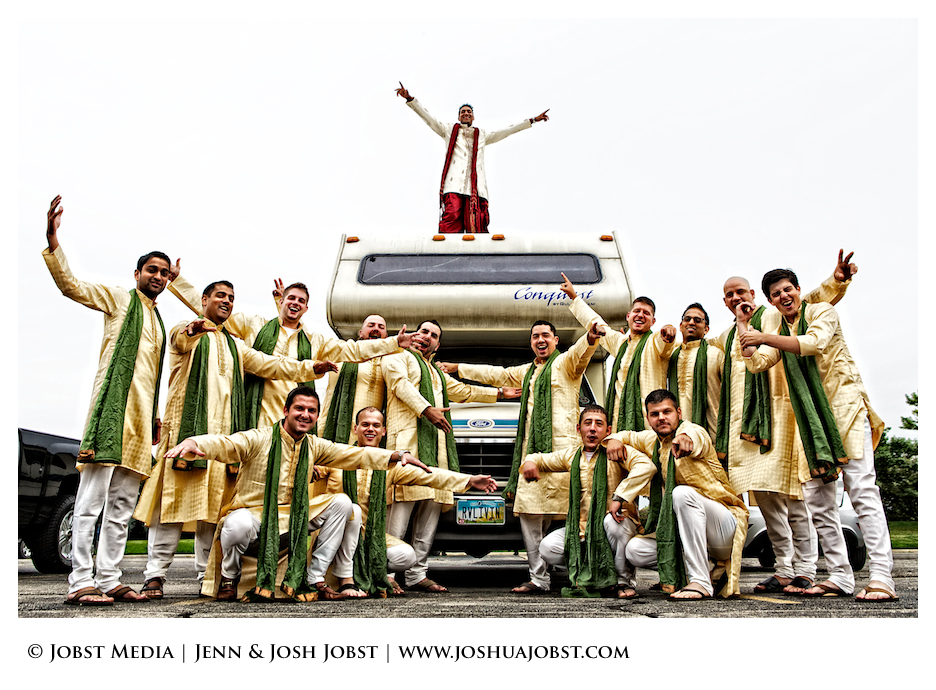 Indian Wedding Photographers Michigan grooms bros are all waving their hands in excitement as they climb up the rv that says on the license plate living rv with groom standing on the top