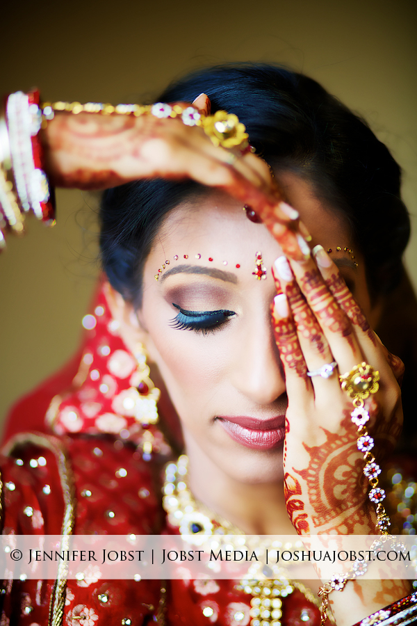 Indian Wedding Photographers amazing pose of an Indian bride as she covers one eye and the other hand is held above her head very interesting bollywood pose